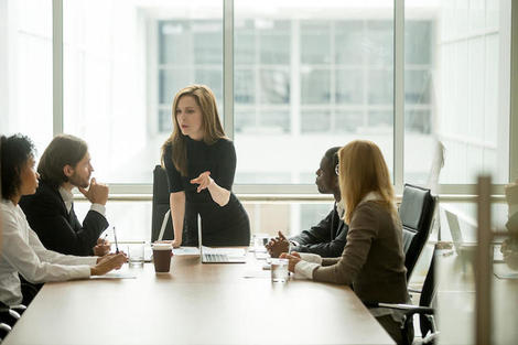 Serious woman boss talking to multiracial team at boardroom meeting