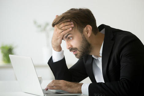 Worried stressed businessman shocked by bad news online using laptop