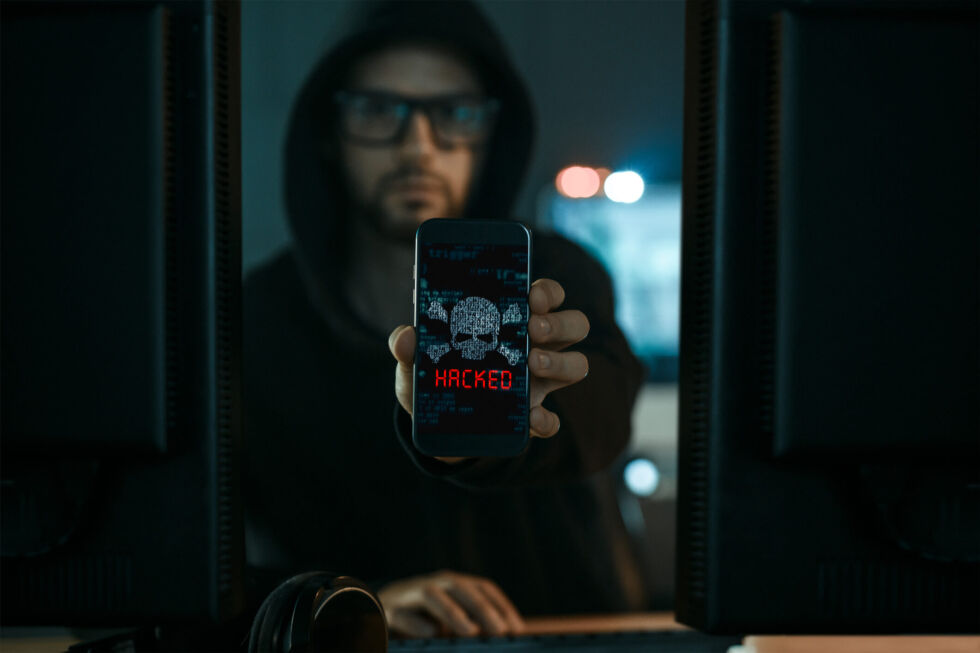 """Artist's impression of a person who has hacked a mobile phone. (In reality, phones don't actually say """"HACKED!"""" to alert you that you've been hacked. Things would be a lot easier if they did.)"""
